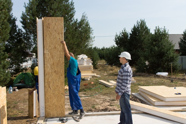 Gruppo di costruttori che montano pannelli di parete in legno coibentati sul pavimento appena posato di una casa di nuova costruzione su un terreno residenziale