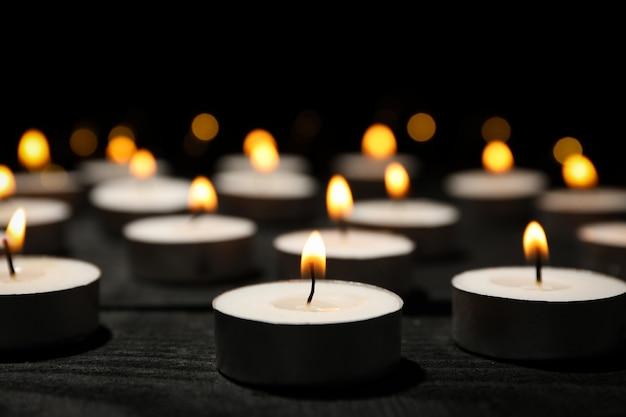 Gruppo di candele brucianti sul nero