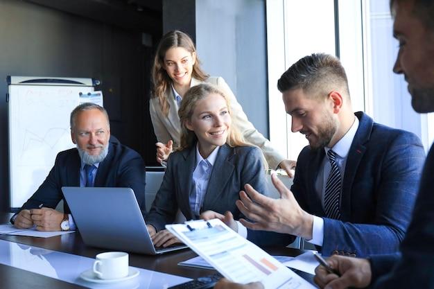 Gruppo di partner commerciali che discutono idee e pianificano il lavoro in ufficio.