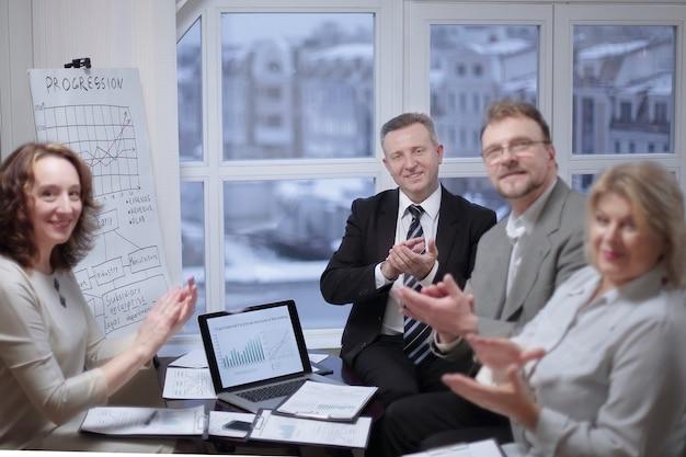 Gruppo di uomini d'affari che applaude altoparlante, seduto in ufficio
