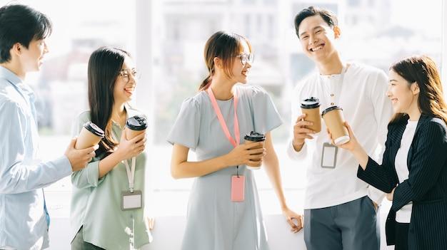 Un gruppo di uomini d'affari sta chiacchierando e bevendo caffè durante la ricreazione
