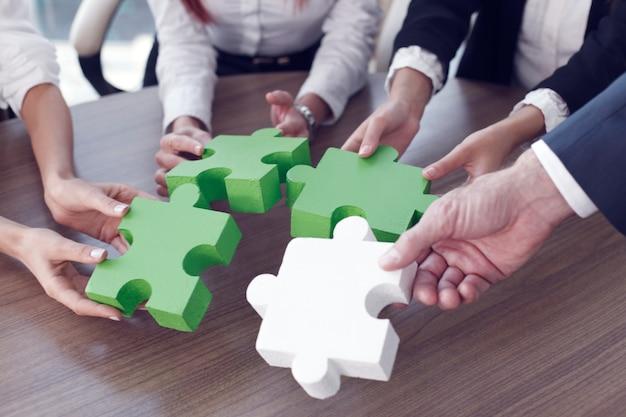 Un gruppo di uomini d'affari che assemblano puzzle e rappresentano il supporto del team e il concetto di aiuto in ufficio