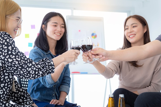 Gruppo di uomini d'affari che tintinnano bicchieri di vino alla festa per una celebrazione aziendale di successo