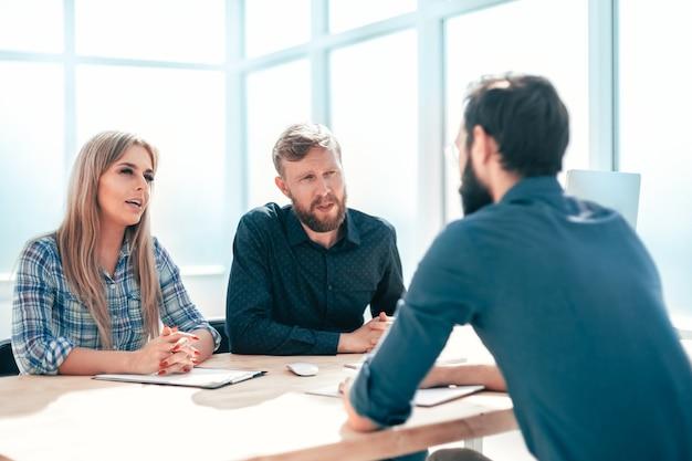 Gruppo di uomini d'affari che conducono un colloquio seduto al tavolo. il concetto di occupazione