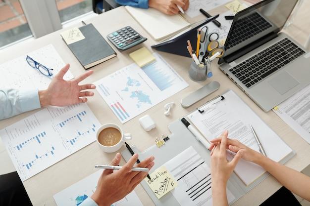 Gruppo di uomini d'affari che discutono grafici e diagrammi durante le riunioni, analizzano i dati di vendita e pianificano il lavoro