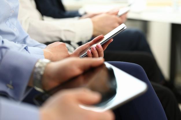 La gente di affari del gruppo tiene il dispositivo mobile