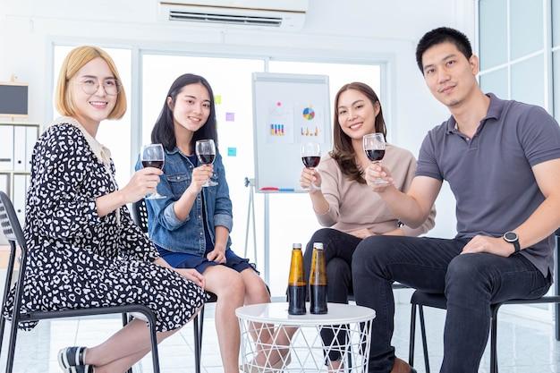 Gruppo di uomini d'affari che tengono bicchieri di vino alla festa per una celebrazione aziendale di successo