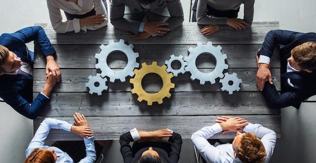 Gruppo di gente di affari che unisce insieme ingranaggi colorati argento e dorato sul tavolo in vista dall'alto sul posto di lavoro