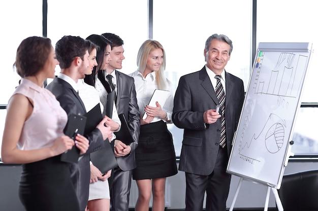Un gruppo di uomini d'affari guardando il grafico sulla lavagna a fogli mobili. avviare