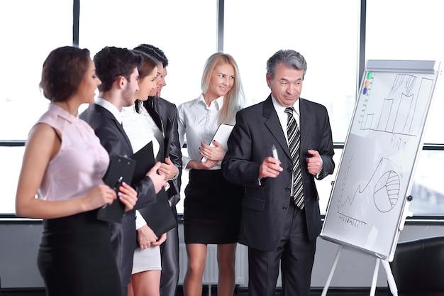 Gruppo di uomini d'affari che guardano il grafico sulla lavagna a fogli mobili