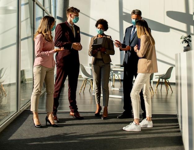 Gruppo di uomini d'affari che si incontrano e lavorano in ufficio e indossano una maschera per proteggere e prevenire l'infezione da virus corona