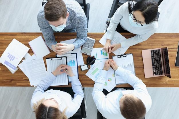 Gruppo di uomini d'affari in maschere protettive seduto al piano del tavolo. conferenza di lavoro durante