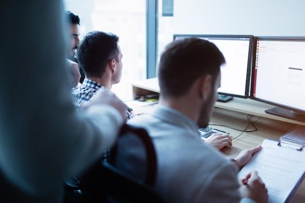 Gruppo di uomini d'affari e sviluppatori di software che lavorano come una squadra in ufficio