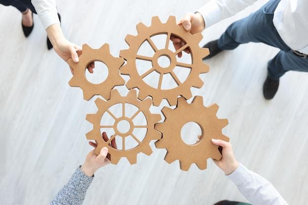 Gruppo di uomini d'affari che impilano vista dall'alto di ingranaggi in legno. concetto di lavoro di squadra