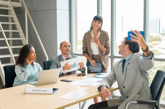 Un gruppo di uomini d'affari che si fanno selfie in ufficio