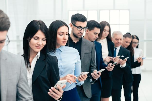 Gruppo di uomini d'affari con smartphone in fila