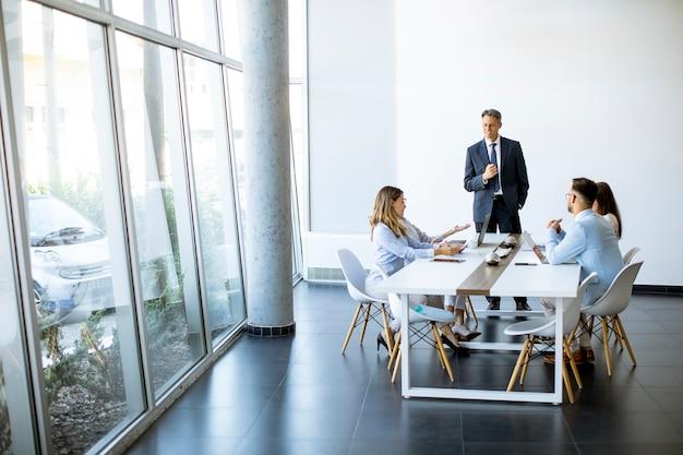 Gruppo di uomini d'affari con giovani adulti e collega senior donna sulla riunione all'interno dell'ufficio moderno e luminoso