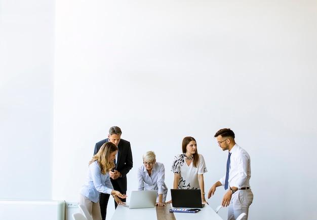 Gruppo di uomini d'affari con giovani adulti e collega donna anziana che si incontrano all'interno dell'ufficio moderno e luminoso