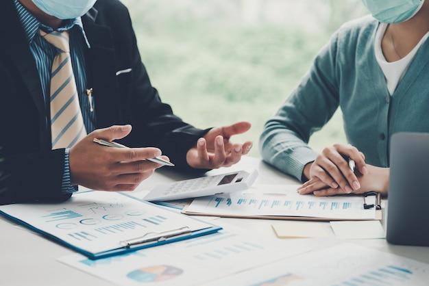 Un gruppo di uomini d'affari e donne d'affari di brainstorming lavorano insieme sul concetto di contabilità lavorano in ufficio. indossa una maschera per prevenire i germi.