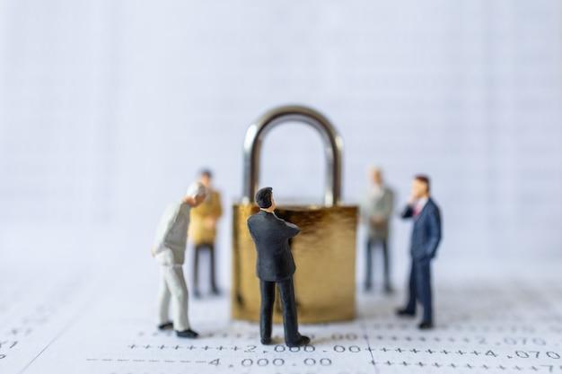 Gruppo di uomini d'affari figura in miniatura persone in piedi intorno alla serratura a chiave master d'oro sul libretto della banca