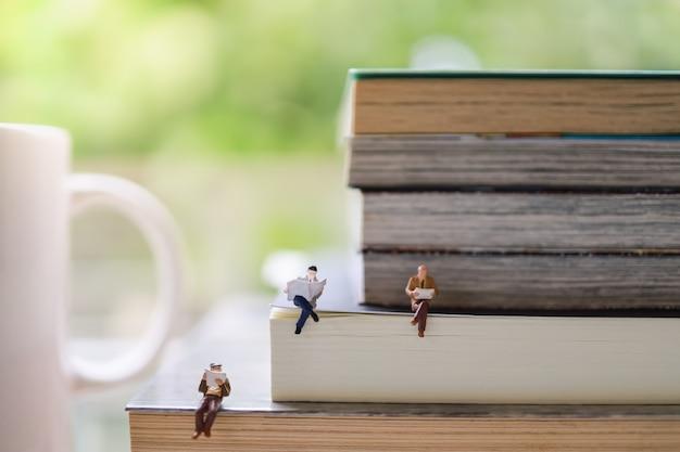 Gruppo di figura miniatura dell'uomo d'affari che si siede e che legge giornale e libro sulla pila di libri con la tazza della tazza di caffè caldo.