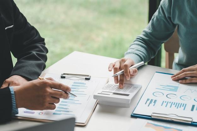 Gruppo di uomini d'affari che si incontrano per analizzare le statistiche contabili utilizzando calcolatrici e grafici in ufficio.