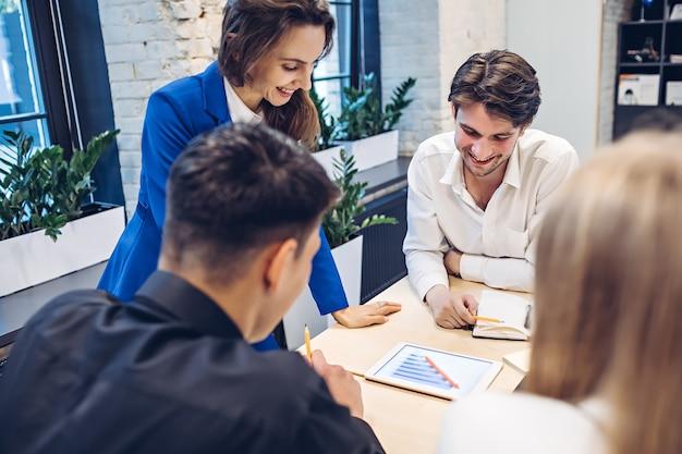 Gruppo di persone di affari che esaminano il grafico di crescita sul tablet al tavolo in ufficio