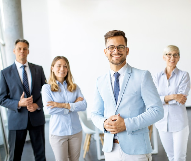 Gruppo di uomini d'affari in piedi insieme in ufficio con il loro giovane leader di affari