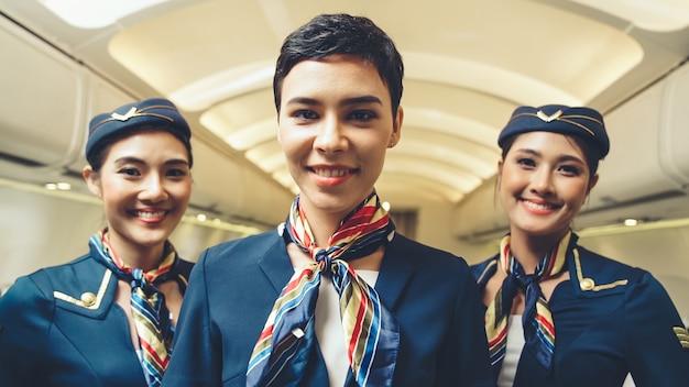 Gruppo di equipaggio di cabina o hostess di volo in aereo. trasporto aereo e concetto di turismo.