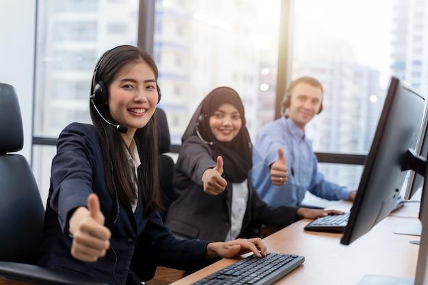 Gruppo di diversità del call center che indossa le cuffie che mostrano i pollici in su lavorando sul computer e parlando con il cliente