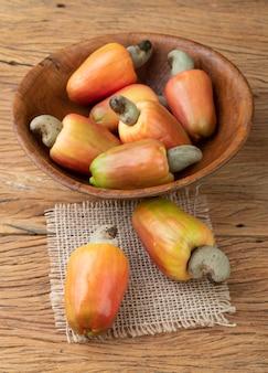 Un gruppo di frutti di anacardi su una ciotola su un tavolo di legno.