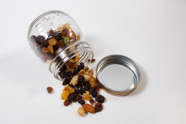 Gruppo di cereali, semi e frutta secca in un contenitore di vetro