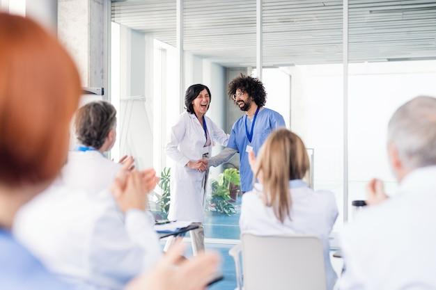 Gruppo di medici allegri in conferenza medica, stringendo la mano.