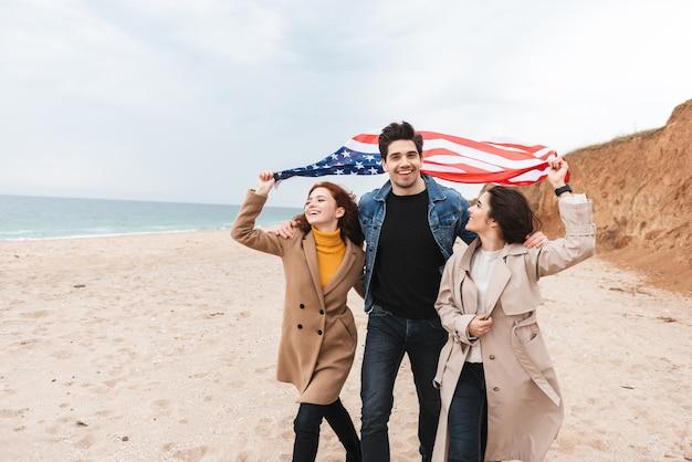 Gruppo di amici allegri che corrono in spiaggia portando bandiera americana