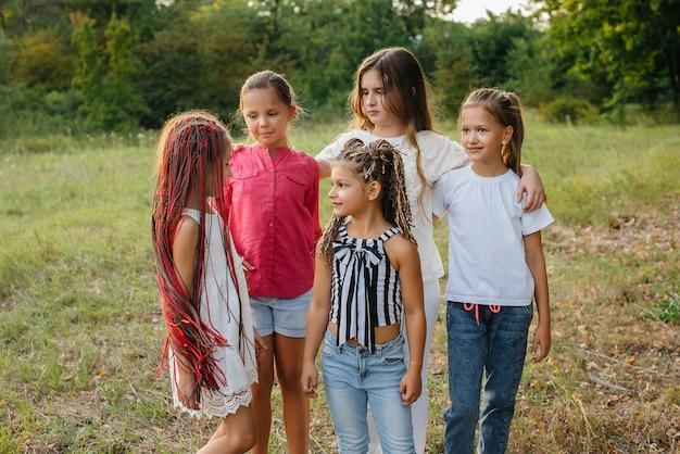 Un gruppo di ragazze allegre sorride e gioca nel parco durante il tramonto. campo estivo per bambini.