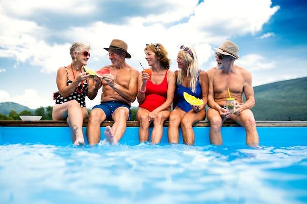Gruppo di anziani allegri seduti a bordo piscina all'aperto in cortile, parlando.