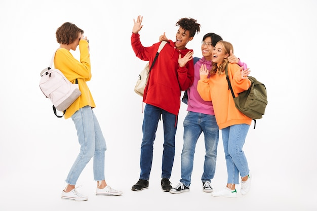 Gruppo di adolescenti allegri isolati, portando zaini, scattare una foto