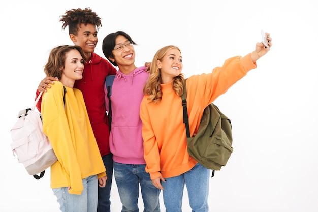 Gruppo di adolescenti allegri isolati, portando zaini, prendendo un selfie