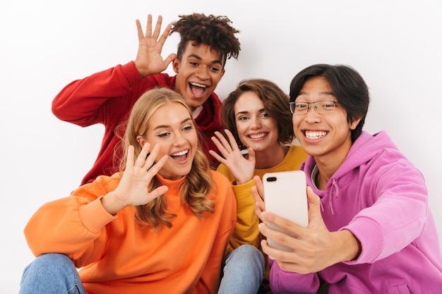 Gruppo di adolescenti allegri isolati, prendendo un selfie