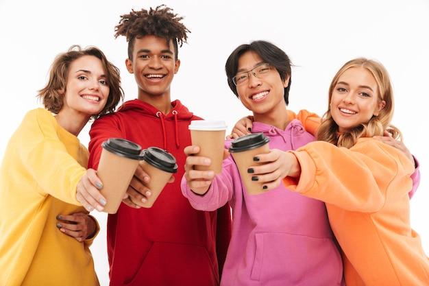 Gruppo di adolescenti allegri isolati, tostando con tazze di caffè
