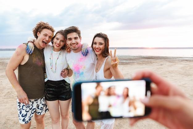 Gruppo di giovani amici allegri che si divertono in spiaggia con vernice colorata holi, farsi fotografare