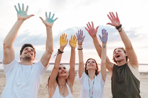 Gruppo di giovani amici allegri che si divertono in spiaggia con vernice colorata holi, mostrando le mani