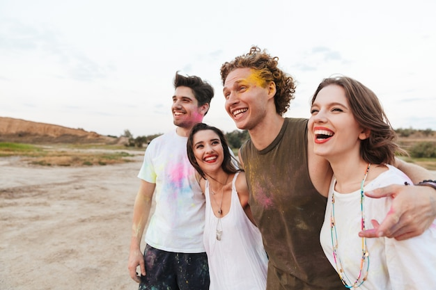 Gruppo di giovani amici allegri che si divertono in spiaggia con colorati holi paint