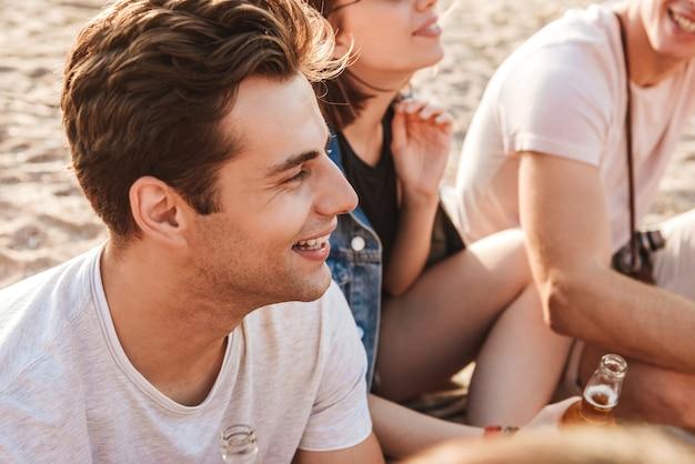 Gruppo di allegri giovani amici divertendosi insieme in spiaggia, bevendo birra, in campeggio