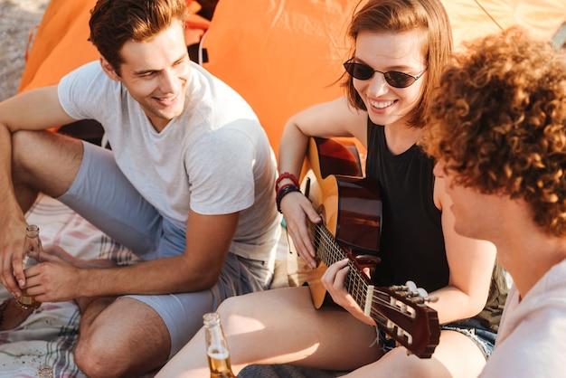 Gruppo di giovani amici allegri che si divertono insieme in spiaggia, bevendo birra, suonando la chitarra durante il campeggio