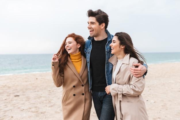 Gruppo di giovani amici allegri che camminano in riva al mare, abbracciati