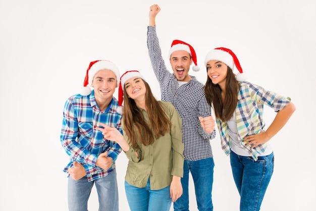 Gruppo di giovani allegri in cappelli della santa che celebrano il natale