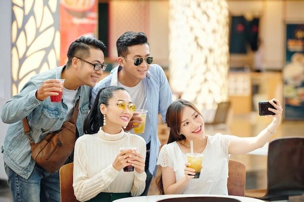 Gruppo di giovani allegri che prendono selfie insieme a cocktaild nelle mani