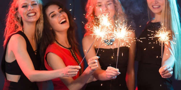 Gruppo di giovani donne allegre che trasportano stelle filanti.