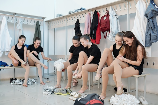 Gruppo di ragazze cheerleading sedute sulle panchine nello spogliatoio e mettendo le scarpe da ballo sui piedi